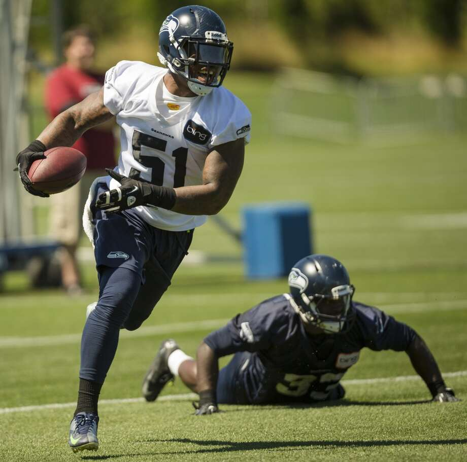 Bruce Irvin, left, laughs after juking out Christine Michael, right, during the opening day of the Seattle Seahawks training camp Thursday, July 25, 2013, at the Virginia Mason Athletic Center in Renton. The sold-out training camp runs through the preseason in August. Nearly 25,000 fans are expected to attend this month. (Jordan Stead, seattlepi.com) Photo: SEATTLEPI.COM