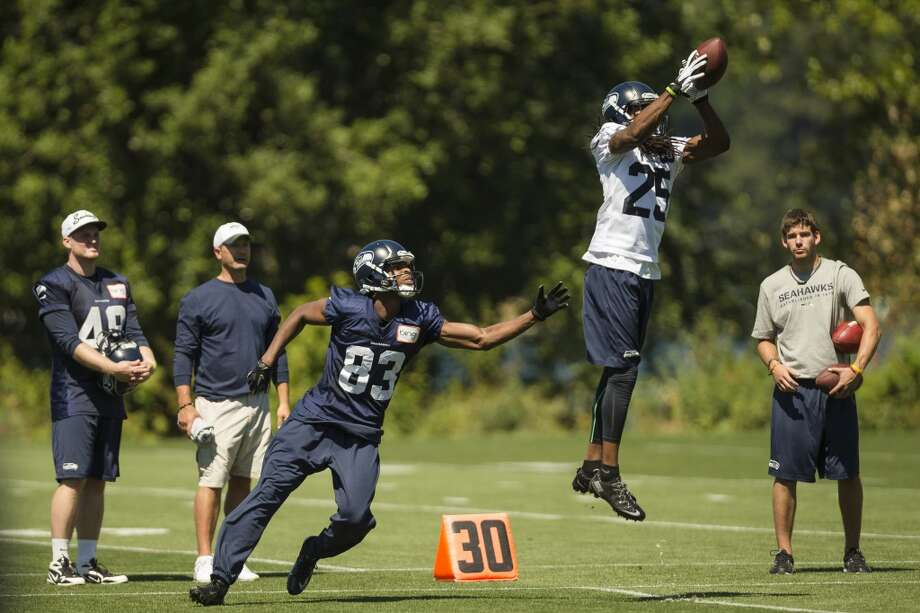 Richard Sherman catches air to make a catch at the opening day of the Seattle Seahawks training camp Thursday, July 25, 2013, at the Virginia Mason Athletic Center in Renton. The sold-out training camp runs through the preseason in August. Nearly 25,000 fans are expected to attend this month. (Jordan Stead, seattlepi.com) Photo: SEATTLEPI.COM