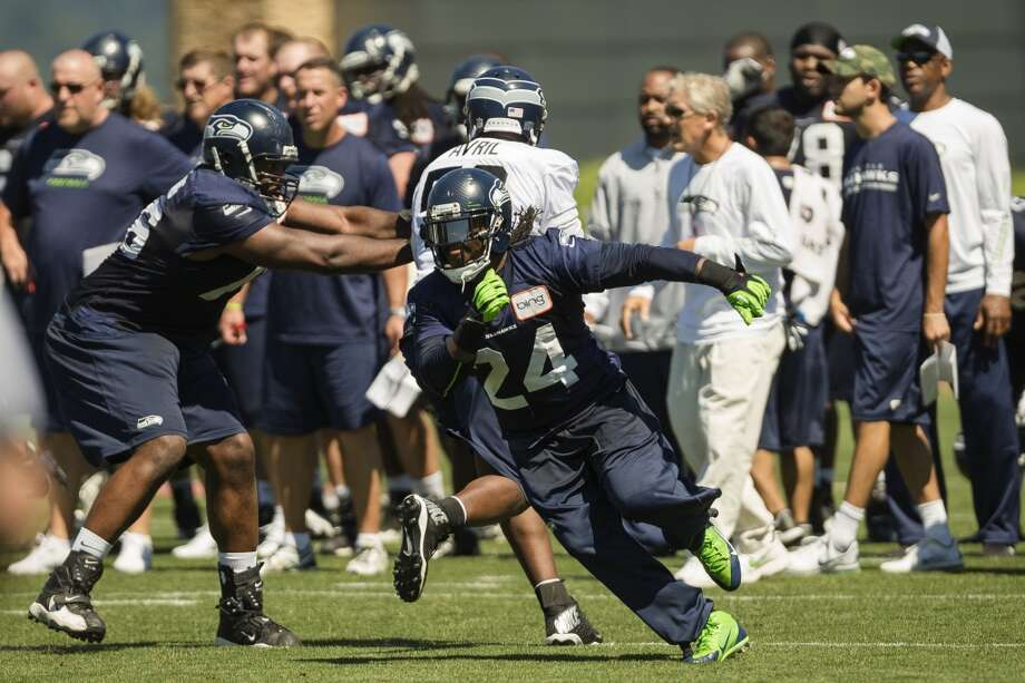 Marshawn Lynch, center, runs through the defensive line during a drill at the opening day of the Seattle Seahawks training camp Thursday, July 25, 2013, at the Virginia Mason Athletic Center in Renton. The sold-out training camp runs through the preseason in August. Nearly 25,000 fans are expected to attend this month. (Jordan Stead, seattlepi.com) Photo: SEATTLEPI.COM