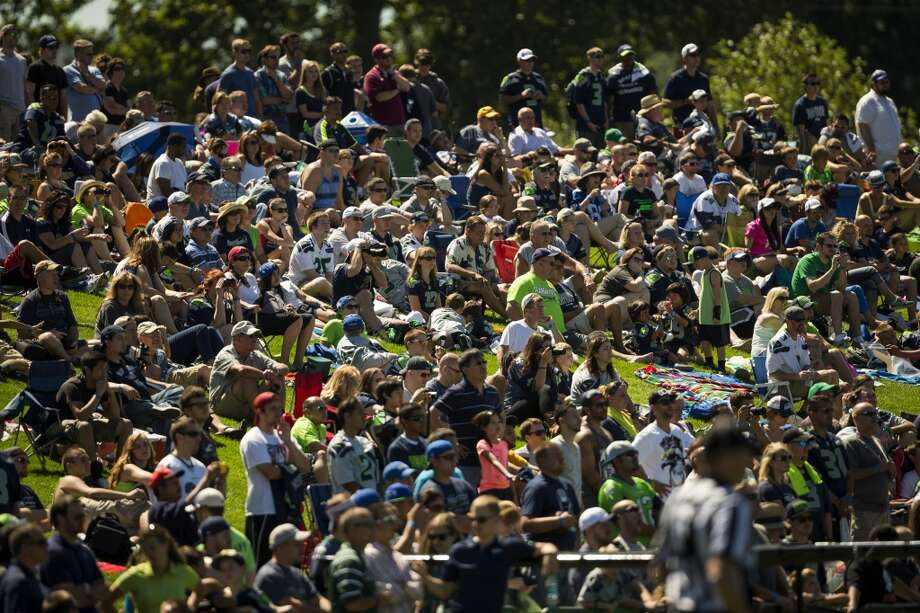 Fans pack a hillside to enjoy the opening day of the Seattle Seahawks training camp Thursday, July 25, 2013, at the Virginia Mason Athletic Center in Renton. The sold-out training camp runs through the preseason in August. Nearly 25,000 fans are expected to attend this month. (Jordan Stead, seattlepi.com) Photo: SEATTLEPI.COM