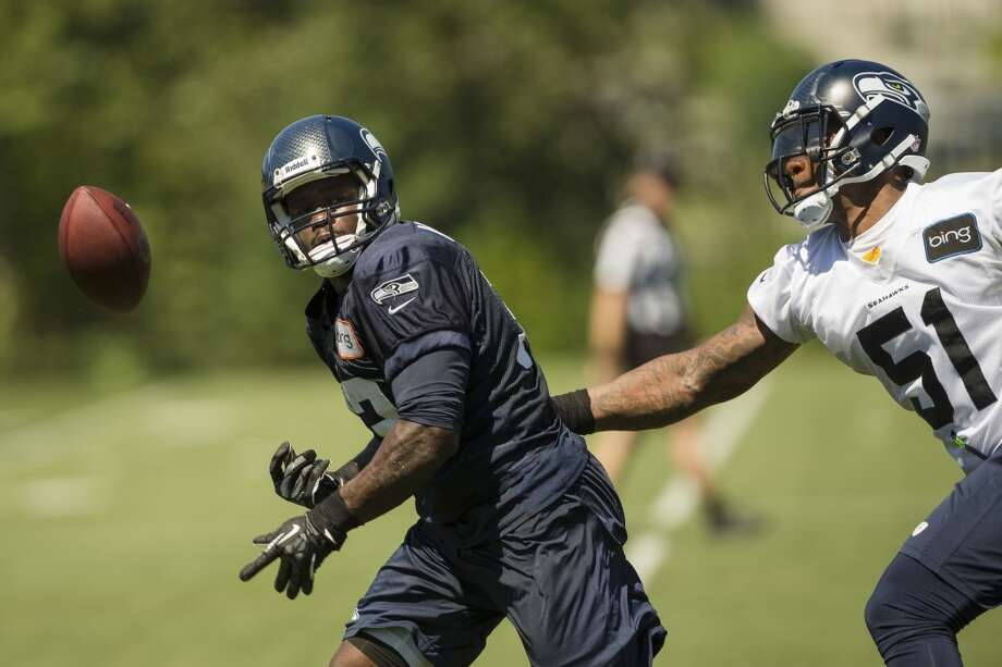Bruce Irvin, right, swipes the ball out from under the arm of Christine Michael, left, during the opening day of the Seattle Seahawks training camp Thursday, July 25, 2013, at the Virginia Mason Athletic Center in Renton. The sold-out training camp runs through the preseason in August. Nearly 25,000 fans are expected to attend this month. (Jordan Stead, seattlepi.com) Photo: SEATTLEPI.COM