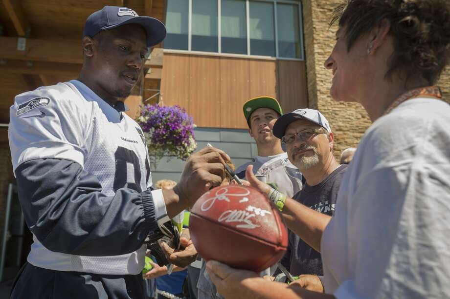 Chris Clemons signs a ball for fans following the opening day of the Seattle Seahawks training camp Thursday, July 25, 2013, at the Virginia Mason Athletic Center in Renton. The sold-out training camp runs through the preseason in August. Nearly 25,000 fans are expected to attend this month. (Jordan Stead, seattlepi.com) Photo: SEATTLEPI.COM