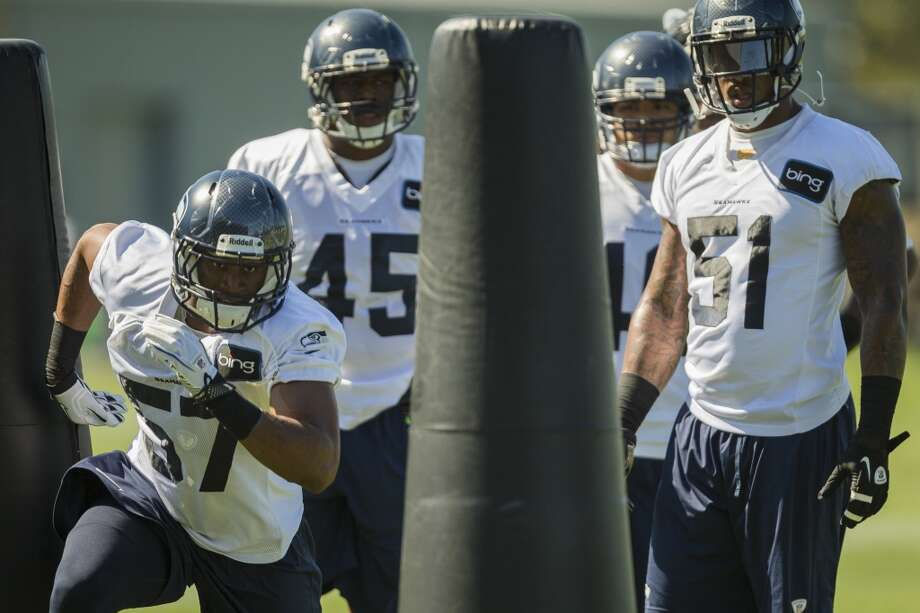 Mike Morgan, left, runs an offensive play with teammates during the opening day of the Seattle Seahawks training camp Thursday, July 25, 2013, at the Virginia Mason Athletic Center in Renton. The sold-out training camp runs through the preseason in August. Nearly 25,000 fans are expected to attend this month. (Jordan Stead, seattlepi.com) Photo: SEATTLEPI.COM