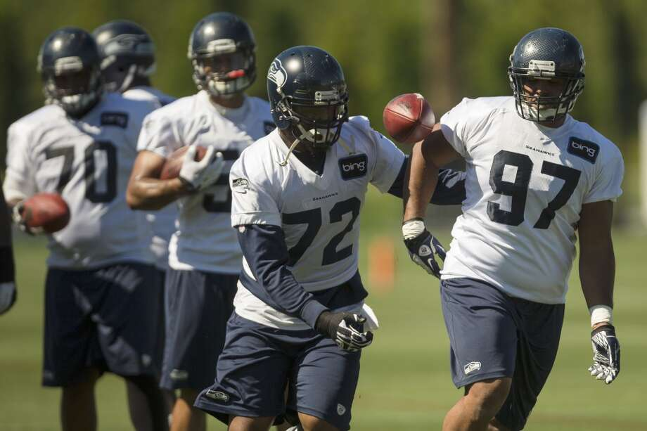 Michael Bennett, center, and Jordan Hill, right, run a play during the opening day of the Seattle Seahawks training camp Thursday, July 25, 2013, at the Virginia Mason Athletic Center in Renton. The sold-out training camp runs through the preseason in August. Nearly 25,000 fans are expected to attend this month. (Jordan Stead, seattlepi.com) Photo: SEATTLEPI.COM