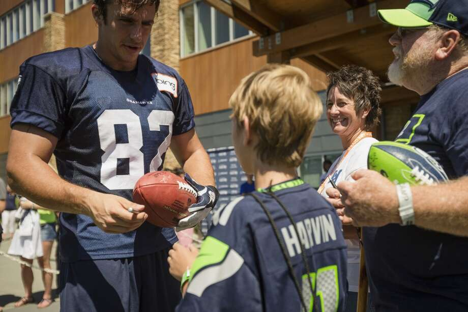 Luke Willson, left, signs a ball for fans following the opening day of the Seattle Seahawks training camp Thursday, July 25, 2013, at the Virginia Mason Athletic Center in Renton. The sold-out training camp runs through the preseason in August. Nearly 25,000 fans are expected to attend this month. (Jordan Stead, seattlepi.com) Photo: SEATTLEPI.COM