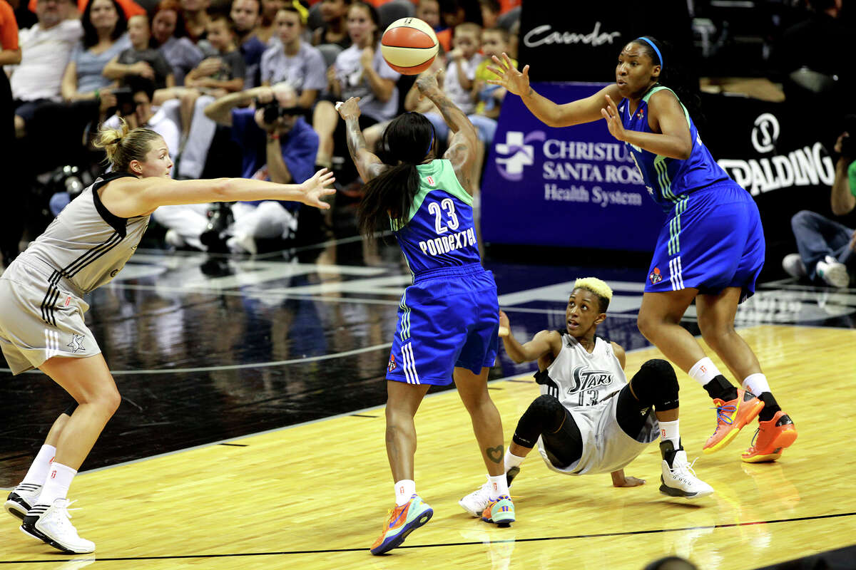 Liberty's Cappie Pondexter, 23, reaches for the ball over Silver Star's Danielle Robinson, 13, at the Silver Stars game against the New York Liberty at the AT&T center on Thursday, July 25, 2013. The Silver Stars won 65 to 53. The win was number 200 for head coach Dan Hughes.