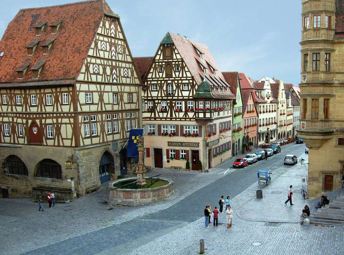 The town fountain is flanked by characteristic half-timbered buildings, once filled with grain and corn to enable the town's inhabitants to survive any siege.