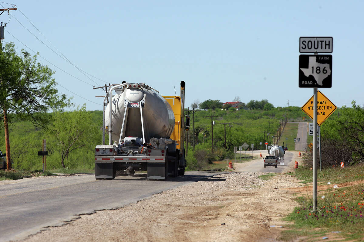 Traffic related to oil and natural gas drilling moves along FM 186 near Carrizo Springs in March. State transportation officials plan to convert 83 miles of paved rural roads back to gravel.