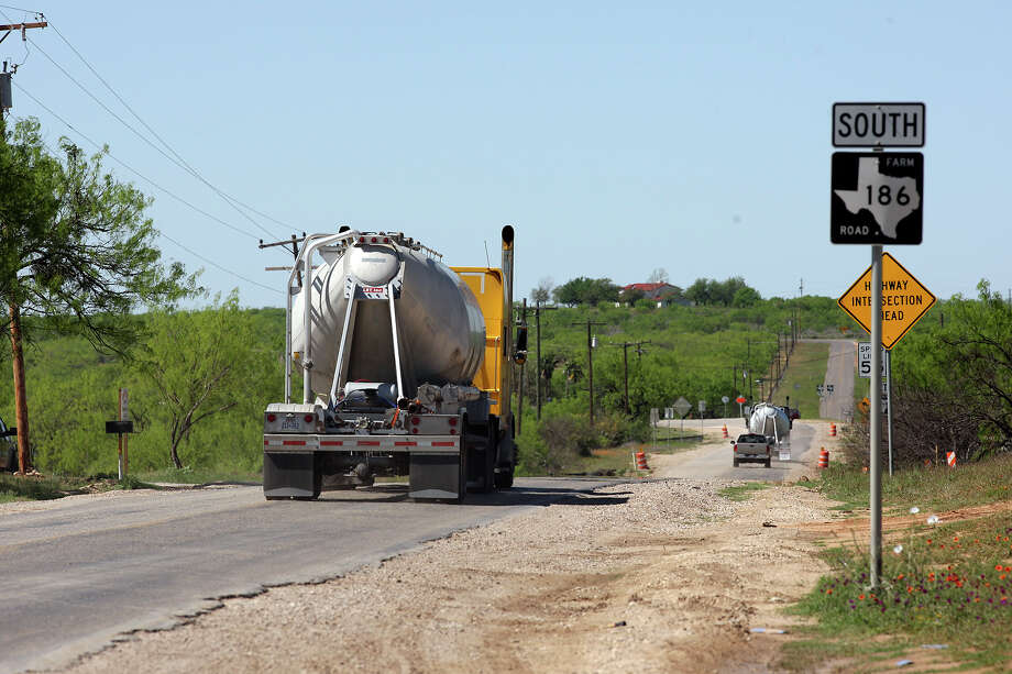 Traffic related to oil and natural gas drilling moves along FM 186 near Carrizo Springs in March. State transportation officials plan to convert 83 miles of paved rural roads back to gravel. Photo: JERRY LARA / SAN ANTONIO EXPRESS-NEWS