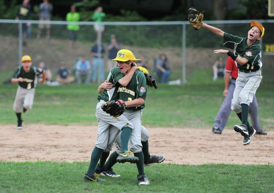 New Milford players, including Hunter Skelly, left, Chris Gesualdi, center, and Taylor Bowe, right, celebrate after thier team's 5-2 win over Exeter, N.H. in the 12-year-old championship game of the Cal Ripken League New England regional tournament at Garick Farms Park in New Milford, Conn. on Thursday, July 25, 2013. Photo: Tyler Sizemore / The News-Times