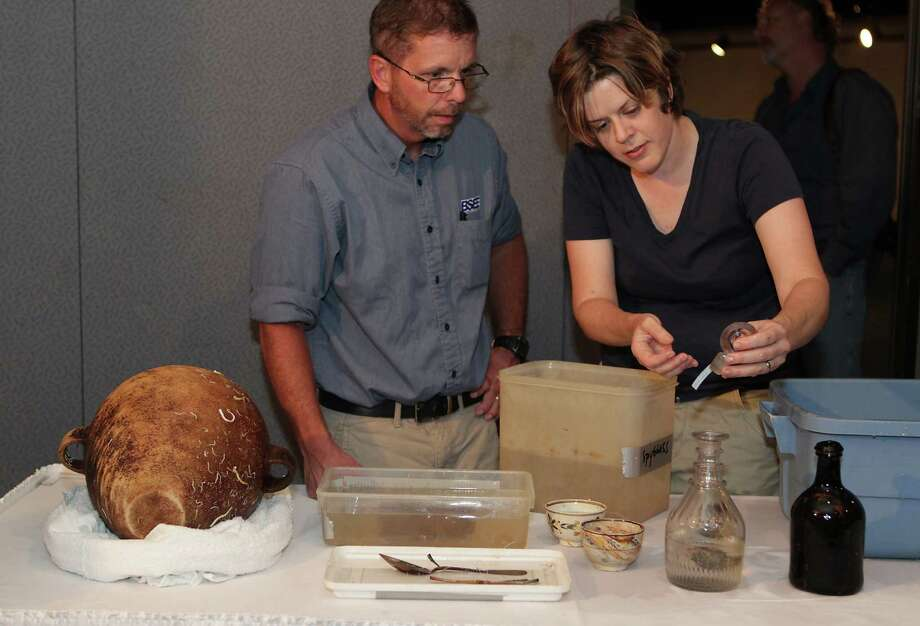 Texas Historical Commisson State Marine Archeologist Amy Borgens right, holds a bottle stopper as BSEE's (Bureau of Safety and Environmental Enforcement) Christopher Horrell left, looks over some of the artifacts excavated from the Monterrey Shipwreck which returned the artifacts to Galveston today from a shipwreck about 170 miles off Galveston, during a press conference at Moody Gardens, Thursday, July 25, 2013, in Galveston. Photo: James Nielsen, Houston Chronicle / © 2013  Houston Chronicle