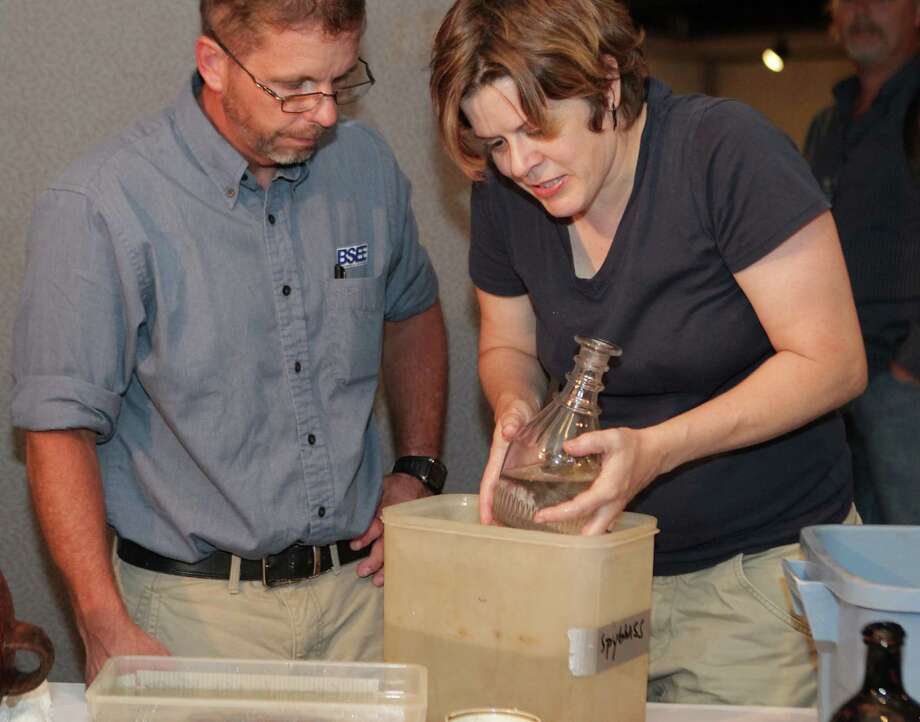 Texas Historical Commisson State Marine Archeologist Amy Borgens right, holds a bottle as BSEE's (Bureau of Safety and Environmental Enforcement) Christopher Horrell left, looks over some of the artifacts excavated from the Monterrey Shipwreck which returned the artifacts to Galveston today from a shipwreck about 170 miles off Galveston, during a press conference at Moody Gardens, Thursday, July 25, 2013, in Galveston. Photo: James Nielsen, Houston Chronicle / © 2013  Houston Chronicle