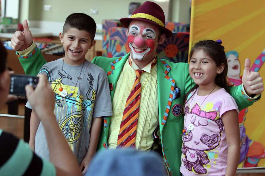 """Matt"" the clown poses with siblings Michael Sifuentes, 8, and patient Michelle Sifuentes, 6, during a visit from members of the Ringling Bros. and Barnum & Bailey's World Famous Clown Alley at M.D. Anderson on Thursday, July 25, 2013, in Houston. Photo: Mayra Beltran, Houston Chronicle / © 2013 Houston Chronicle"