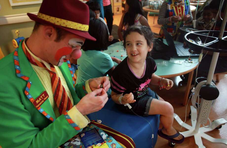 """Matt"" the clown helps patient Kaitlynn Jones, 6, assemble her courage bead necklace during a visit from members of the Ringling Bros. and Barnum & Bailey's World Famous Clown Alley at M.D. Anderson on Thursday, July 25, 2013, in Houston. Photo: Mayra Beltran, Houston Chronicle / © 2013 Houston Chronicle"