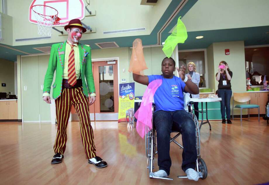 """Matt"" the clown teaches Dalvin Davis, 15, how to juggle during a visit from members of the Ringling Bros. and Barnum & Bailey's World Famous Clown Alley at M.D. Anderson on Thursday, July 25, 2013, in Houston. Photo: Mayra Beltran, Houston Chronicle / © 2013 Houston Chronicle"