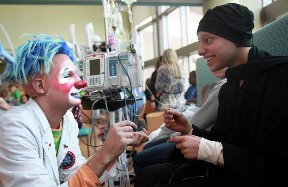 """DJ"" the clown helps patient Ghada Alsubaey assemble her courage bead necklace during a visit from members of the Ringling Bros. and Barnum & Bailey's World Famous Clown Alley at M.D. Anderson on Thursday, July 25, 2013, in Houston. Photo: Mayra Beltran, Houston Chronicle / © 2013 Houston Chronicle"