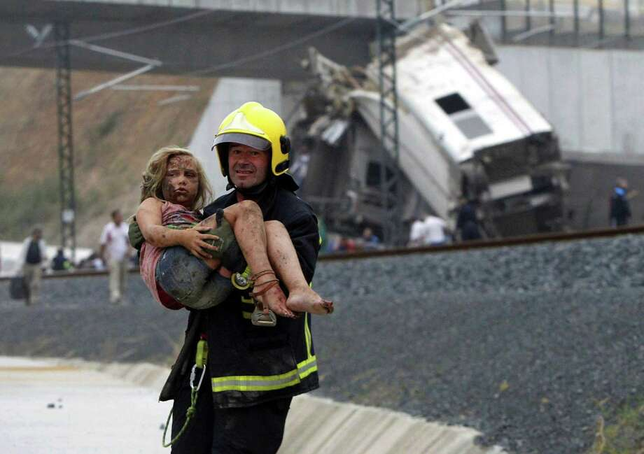 A firefighter carries a young girl bloodied from head to toe following the train accident near the city of Santiago de Compostela, Spain. The death toll is approaching triple figures with dozens in critical condition. Photo: Xoan A. Soler / La Voz De Galicia