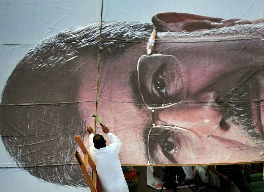 A supporter of deposed Egyptian President Mohammed Morsi builds a giant portrait of him as other supporters participate in a sit-in outside Rabaa al-Adawiya mosque in Cairo. Photo: Fayez Nureldine / Getty Images