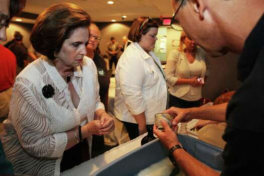 A news conference Thursday at Moody Gardens offered a glimpse of items brought up from the Gulf's floor, like this small bowl shown to Carmela Frels, left, by Frank Cantelas of the National Oceanic and Atmospheric Administration. Photo: James Nielsen, Staff / © 2013  Houston Chronicle