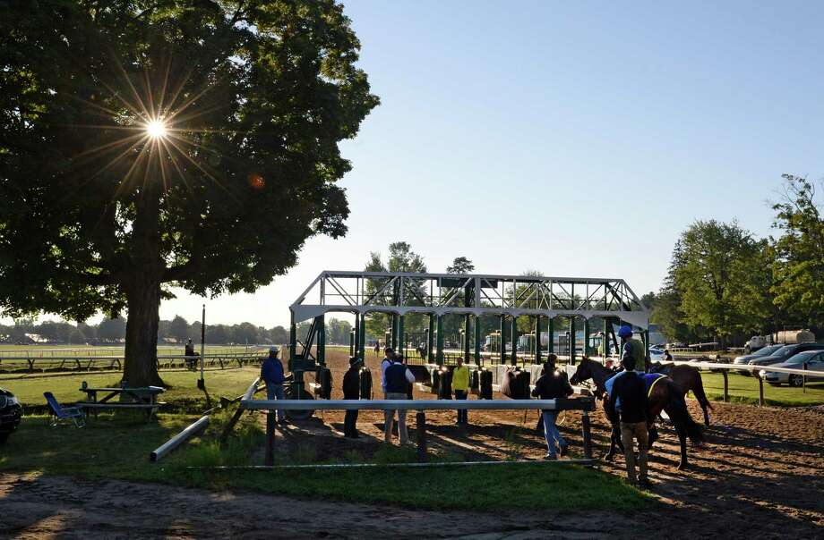 As the sun peeks through the tree gate, training is in full swing Thursday morning, July 25, 2013, at the Oklahoma Training Center in Saratoga Springs, N.Y.  (Skip Dickstein/Times Union) Photo: SKIP DICKSTEIN
