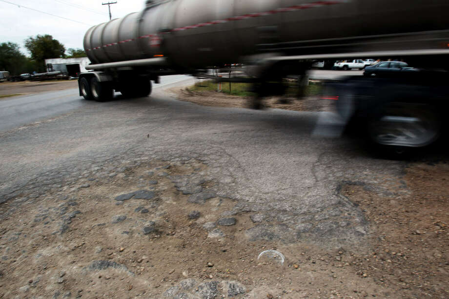 A tanker truck rolls over crumbling asphalt near the intersection of Texas 19 and Texas 72 in Yorktown. Heavy drilling traffic has damaged numerous South Texas roads. Photo: John Davenport / San Antonio Express-News