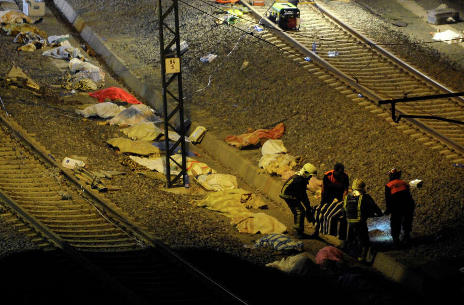 Rescuers carry the body of a victim as other bodies covered with blankets lie on the ground, near the city of Santiago de Compostela on July 24, 2013. At least 35 people died and 200 people were injured when a train derailed in Galicia in northwestern Spain today, the president of the regional government of Galicia said. The train which carried 238 passengers originated in Madrid and was bound for the northwestern town of Ferrol. Photo: MIGUEL RIOPA, AFP/Getty Images / 2013 AFP