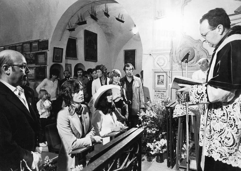 14th May 1971, British rock musician Mick Jagger kneels next to his bride, Bianca Jagger, during their wedding ceremony, as French director Roger Vadim and Nathalie Delon look on. Photo: Express, Getty Images / Archive Photos