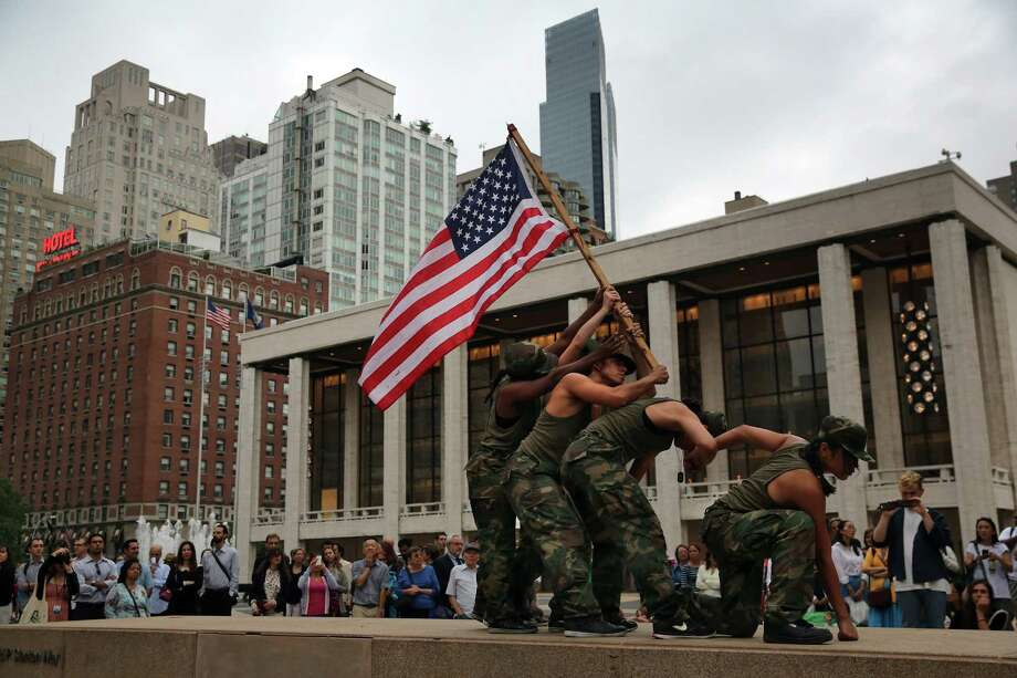 "NEW YORK, NY - JULY 25:  Female dancers dressed as U.S. National Guard soldiers re-enact the iconic image ""Raising the Flag on Iwo Jima"" while performing choreographer Mark Dendy's ""Ritual Cyclical"", presented by Lincoln Center Out of Doors and the American Dance Festival on July 25, 2013 in New York City. Eighty dancers took part in the site specific event at the Lincoln Center's Hearst Plaza. The flag raising scene was modeled on the photograph taken in 1945 by Joe Rosenthal of the Associated Press, who won the Pulitzer Prize for the  image. (Photo by John Moore/Getty Images) ORG XMIT: 174542921 Photo: John Moore, Getty / 2013 Getty Images"