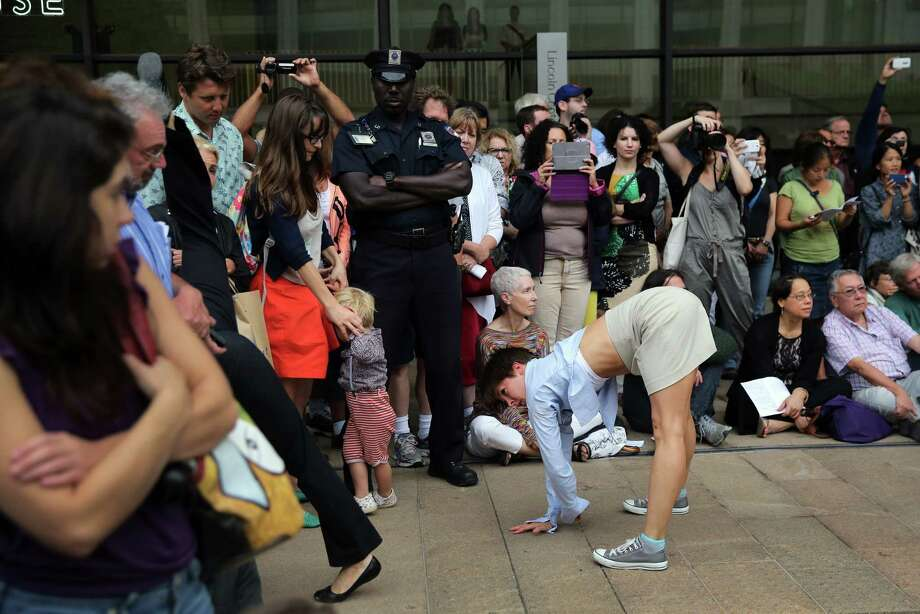 """NEW YORK, NY - JULY 25:  The public watches as dancers perform choreographer Mark Dendy's """"Ritual Cyclical"""", presented by Lincoln Center Out of Doors and the American Dance Festival on July 25, 2013 in New York City. Eighty dancers took part in the site specific event at the Lincoln Center's Hearst Plaza in performances Wednesday and Thursday.  (Photo by John Moore/Getty Images) ORG XMIT: 174542921 Photo: John Moore, Getty / 2013 Getty Images"""