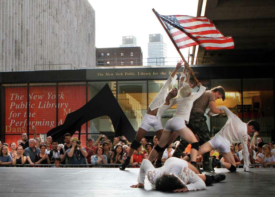 """Dancers perform on a stage at New York's Lincoln Center on Wednesday, July 24, 2013, as part of a show titled """"Ritual Cyclical."""" The event features 80 dancers in and around the plaza, throughout the audience and even in the fountain. It extends through Thursday, July 25. (AP Photo/Jon Gerberg) ORG XMIT: NYJG106 Photo: Jon Gerberg, AP / AP"""
