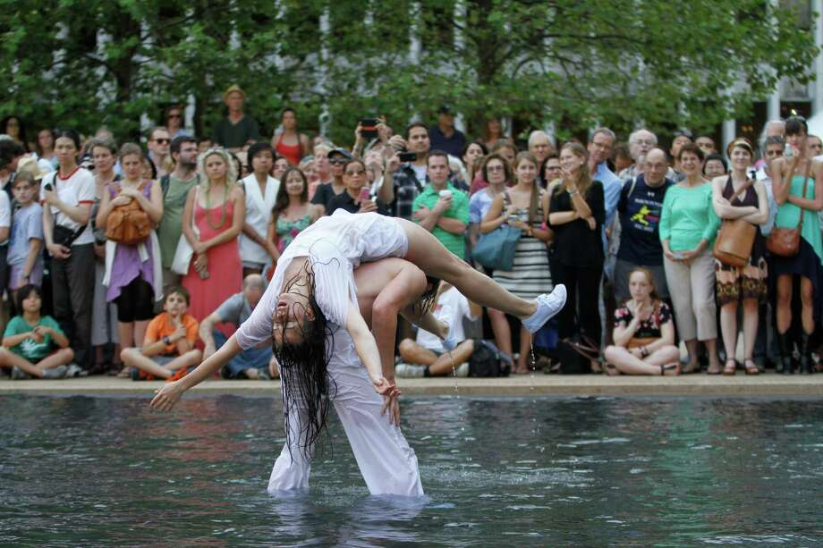 "Husband and wife dancing duo Colette Krogol and Matthew Reeves perform in a fountain at New York's Lincoln Center on Wednesday, July 24, 2013. Titled ""Ritual Cyclical,"" the event features 80 dancers in and around the plaza, throughout the audience and even in the fountain. It extends through Thursday, July 25. (AP Photo/Jon Gerberg) ORG XMIT: NYJG103 Photo: Jon Gerberg, AP / AP"