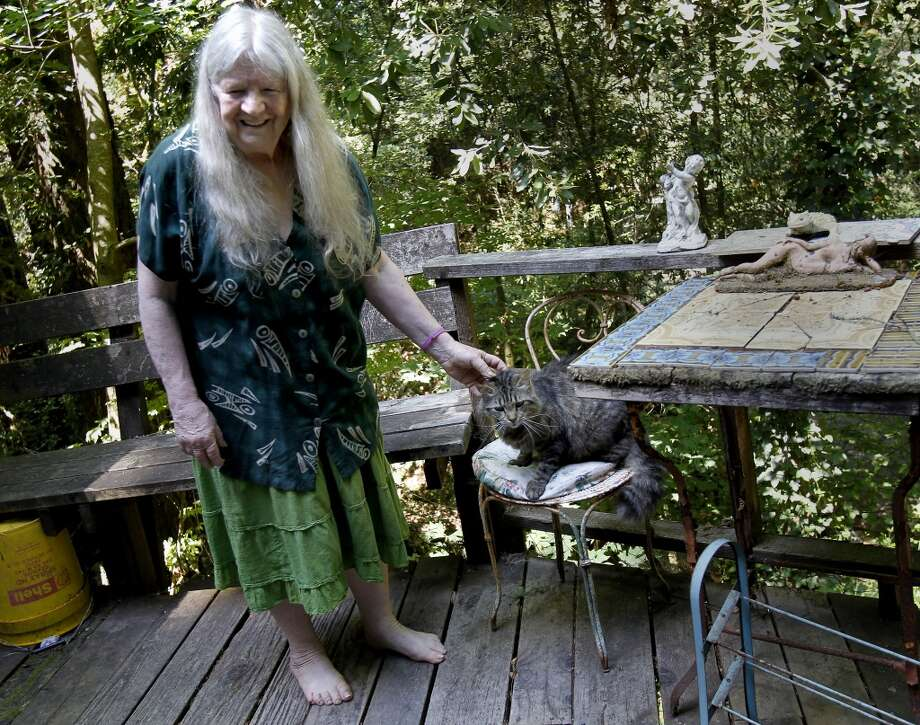 Mary Moore stops to pet George, her cat, who is annoyed with her new dog Wednesday July 24, 2013 at her Camp Meeker home. Mary Moore, the longtime leader of the Bohemian Grove Action Network, is boycotting her own protests because another group run by a Tea Party advocate is horning in on her territory.  Moore plans to continue to attack the rich and powerful men using writings. Photo: The Chronicle