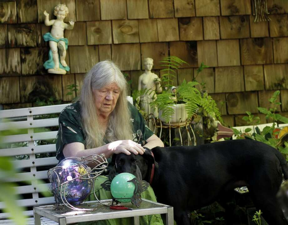 "Mary Moore calms her new pet ""Cota"" Wednesday July 24, 2013, whom she recently adopted. Mary Moore, the longtime leader of the Bohemian Grove Action Network, is boycotting her own protests because another group run by a Tea Party advocate is horning in on her territory.  Moore plans to continue to attack the rich and powerful men using writings. Photo: The Chronicle"