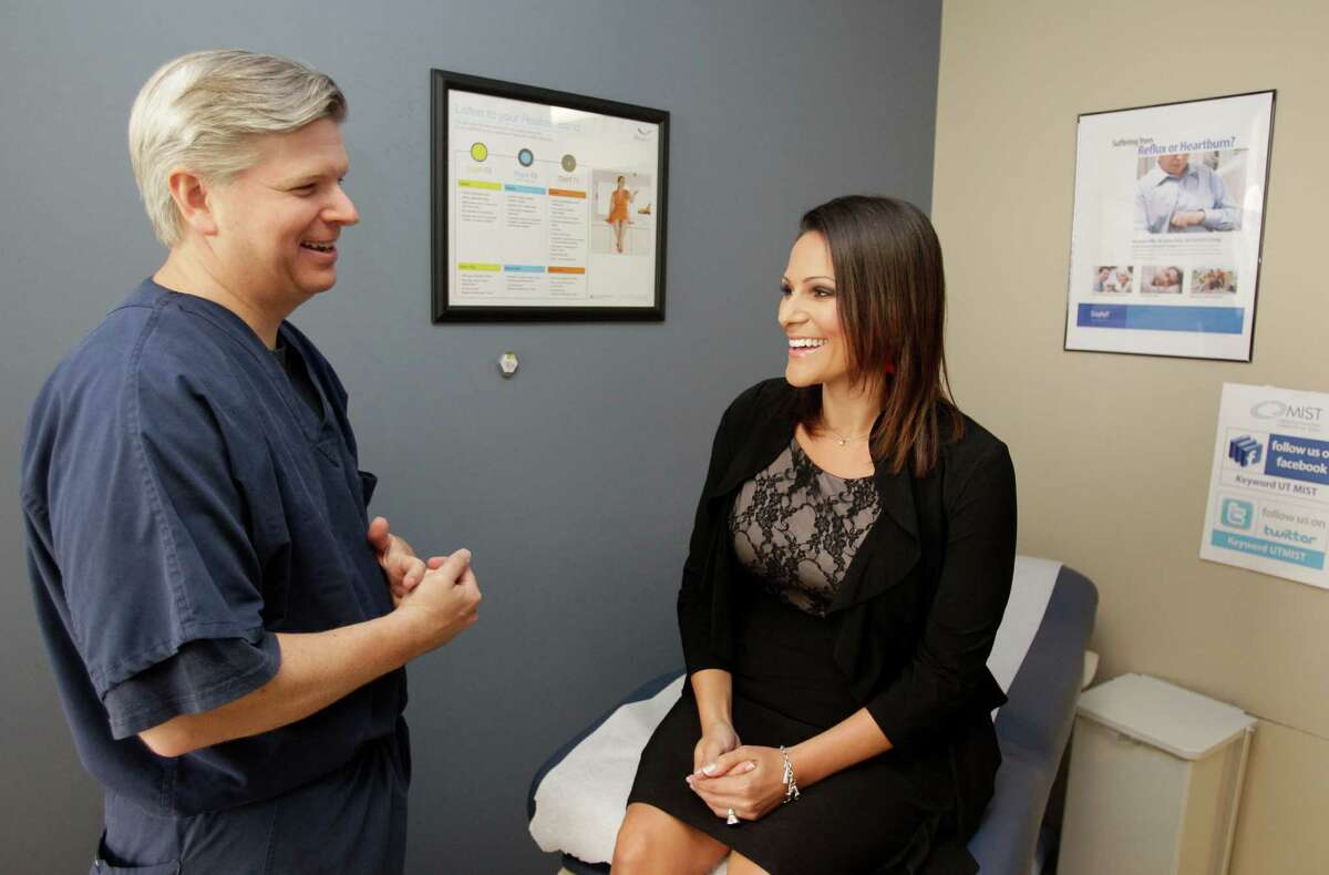 Dr. Erik Wilson confers with patient Ashley Falco during a visit to the UT Health Center. Falco lost 95 pounds after undergoing bariatric surgery in 2011.
