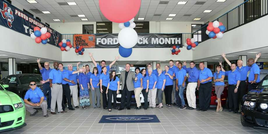 "Jason Mosley (center, in jacket), general manager of AutoNation Ford Katy, said he tells his staff if they aim at being No. 1 every day, the financials will take care of themselves. The dealership has earned back-to-back ""President's Awards"" — Ford's highest honor — since Mosley took the helm of what was formerly known as Champion Ford Katy."