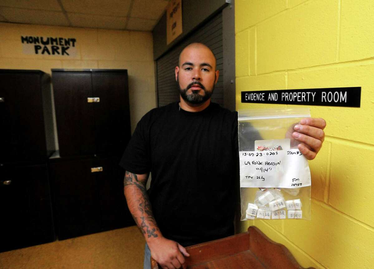 Narcotics officer Luis Vidal displays a bag of confiscated heroin outside the evidence room at the Stamford Police Station in Stamford, Conn. on Friday July 26, 2013.