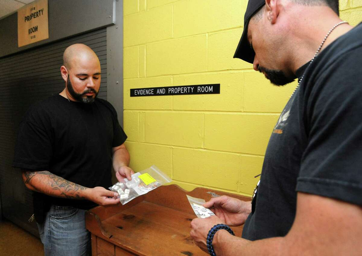 Narcotics officers Luis Vidal and Louis Searano display confiscated heroin outside the evidence room at the Stamford Police Station in Stamford, Conn. on Friday July 26, 2013.