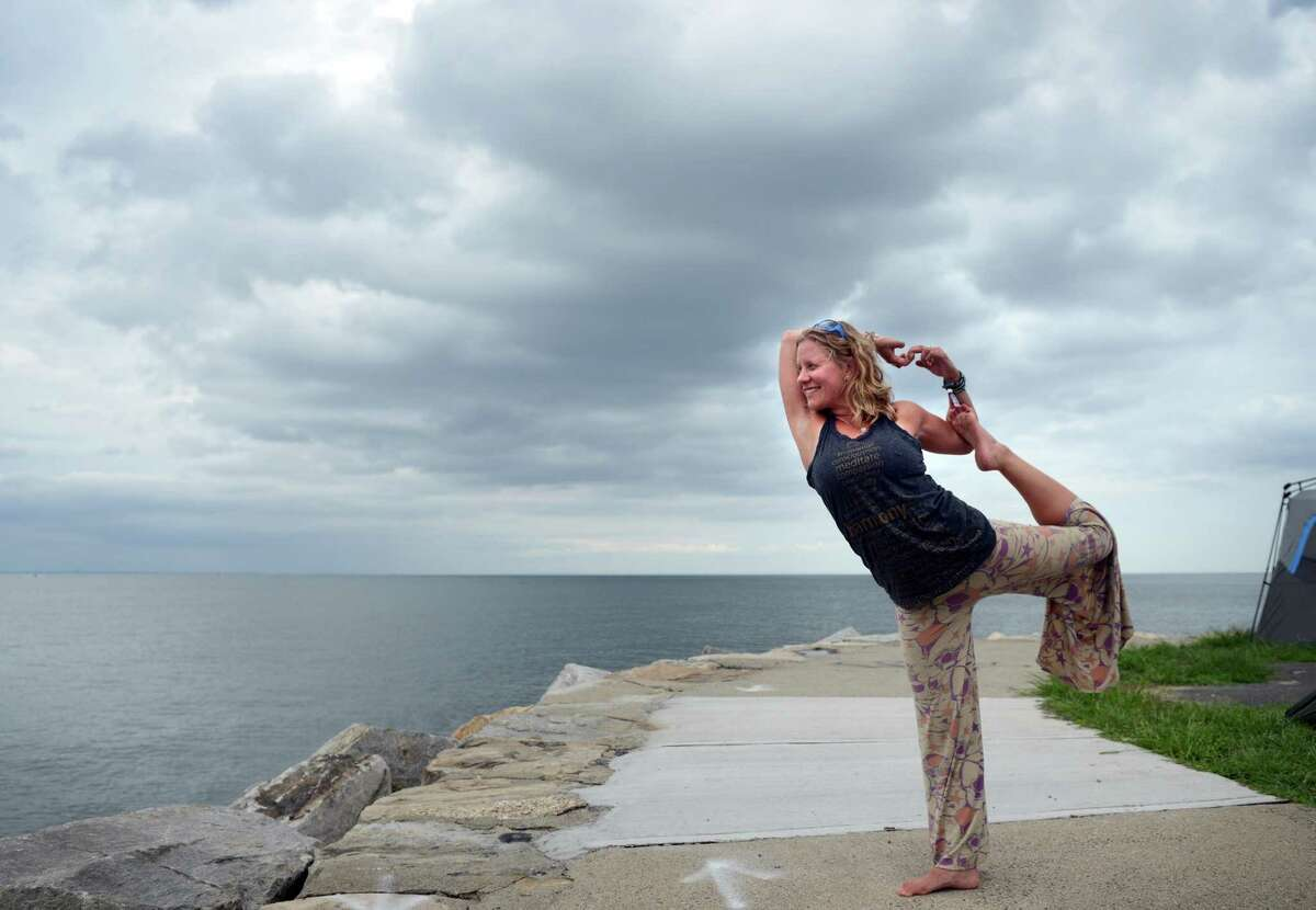 Katie Feinstein faces the Long Island Sound as she practices yoga at the annual Gathering of the Vibes Musical Festival at Seaside Park in Bridgeport, Conn. Friday, July 26, 2013.