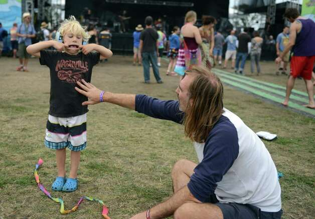 Bonham O'Marra, 4, of Bethel, makes a funny face at his dad, John O'Marra, Friday, July 26, 2013 on the lawn at Seaside Park in Bridgeport, Conn. during the 18th annual Gathering of the Vibes Musical Festival. Photo: Autumn Driscoll / Connecticut Post freelance