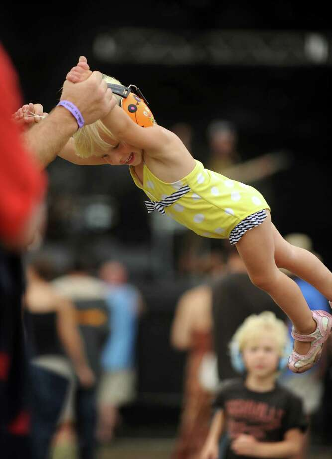 Two-year-old Redding O'Marra, of Bethel, wears protective headphones as she swings with her dad and listens to the music at the 18th annual Gathering of the Vibes Musical Festival at Seaside Park in Bridgeport, Conn. Friday, July 26, 2013. Photo: Autumn Driscoll / Connecticut Post freelance