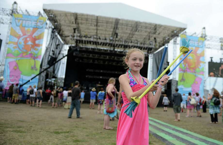 Paige Enright, 10, of Point Pleasant, NJ, plays with devil sticks as she listens to the music at the 18th annual Gathering of the Vibes Musical Festival at Seaside Park in Bridgeport, Conn. Friday, July 26, 2013. Photo: Autumn Driscoll / Connecticut Post freelance