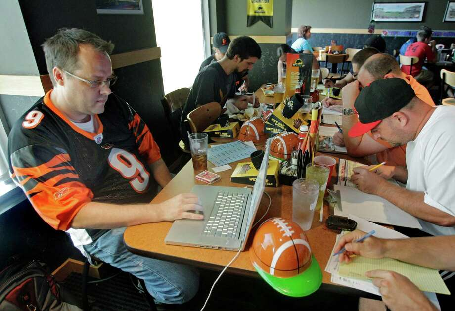 "Fantasy sports analyst Matthew Berry shares stories about fantasy leagues that turn into obsessions in his latest book, ""Fantasy Life."" These fans in Cincinnati are drafting their fantasy football teams. Photo: Al Behrman, STF / AP2010"