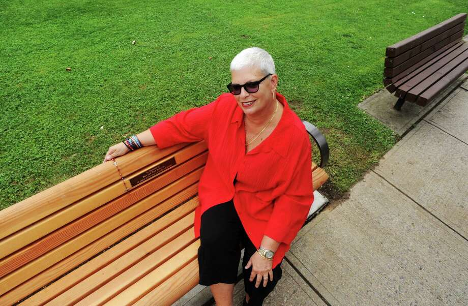 Toni Kokoros sits on a bench in Latham Park that honors her father Constantine Kokoros and his 40 years of service operating Tino's Luncheonette on Bedford Street in Stamford, Conn. Photo: Cathy Zuraw / Stamford Advocate