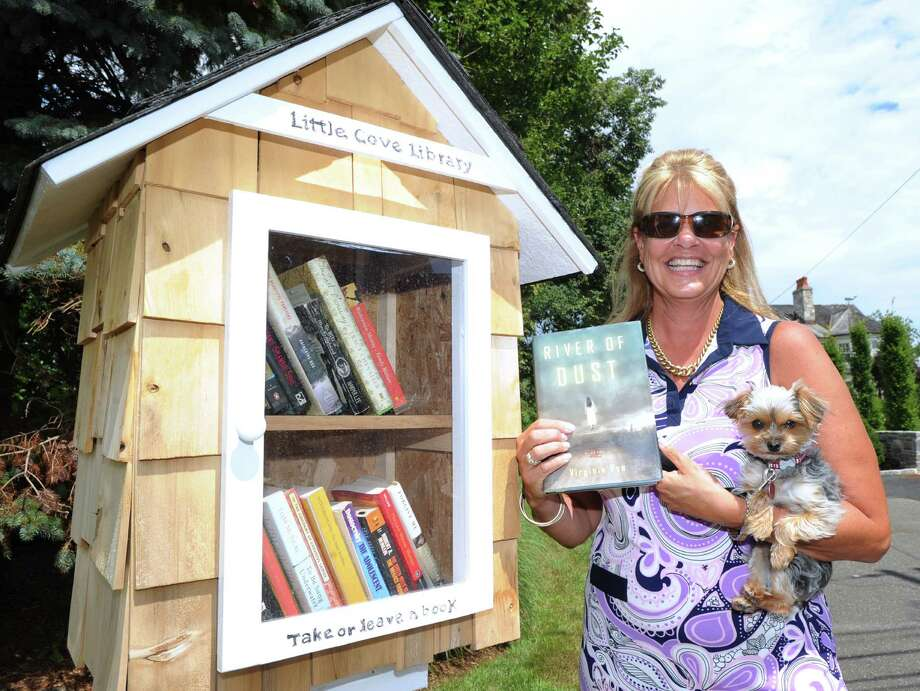 "Sue Rohrer holds her dog, Crumb, and the book ""River of Dust,"" by Virginia Pye, as she stands next to her new ""Little Cove Library,"" a pop-up library, that she has placed on her property at 3 Little Cove Place in Old Greenwich, Friday afternoon, July 26, 2013. Rohrer said anyone is welcome to take out books or add to the collection. Photo: Bob Luckey / Greenwich Time"