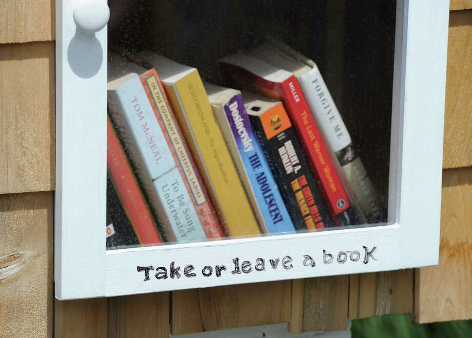 """Take or leave a book,"" reads the sign on the door of Sue Rohrer's  new ""Little Cove Library,"" a pop-up library, that she has placed on her property at 3 Little Cove Place in Old Greenwich, Friday afternoon, July 26, 2013. Rohrer said anyone is welcome to use the library. Photo: Bob Luckey / Greenwich Time"