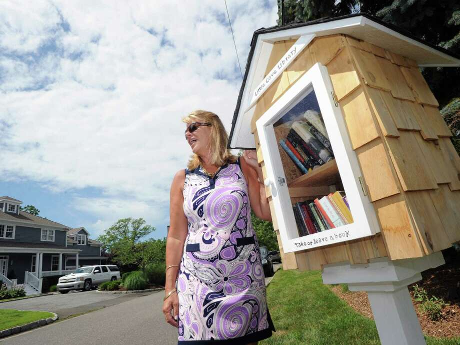 "Sue Rohrer stands next to her new ""Little Cove Library,"" a pop-up library, that she has placed on her property at 3 Little Cove Place in Old Greenwich, Friday afternoon, July 26, 2013. Rohrer said anyone is welcome to take out books or add to the collection. Photo: Bob Luckey / Greenwich Time"