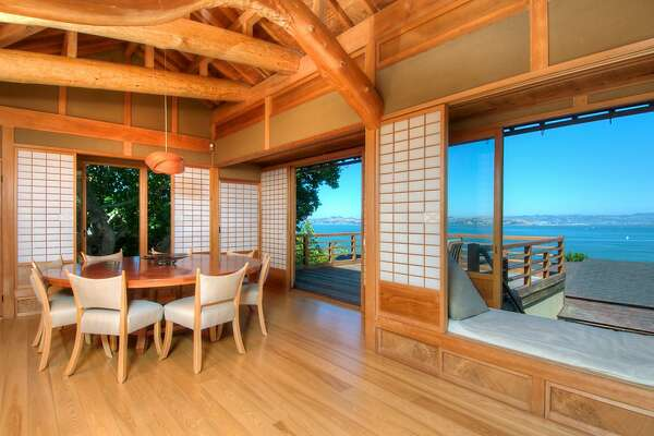 The formal dining room opens to a deck and is decorated by Shoji screens and bay views.