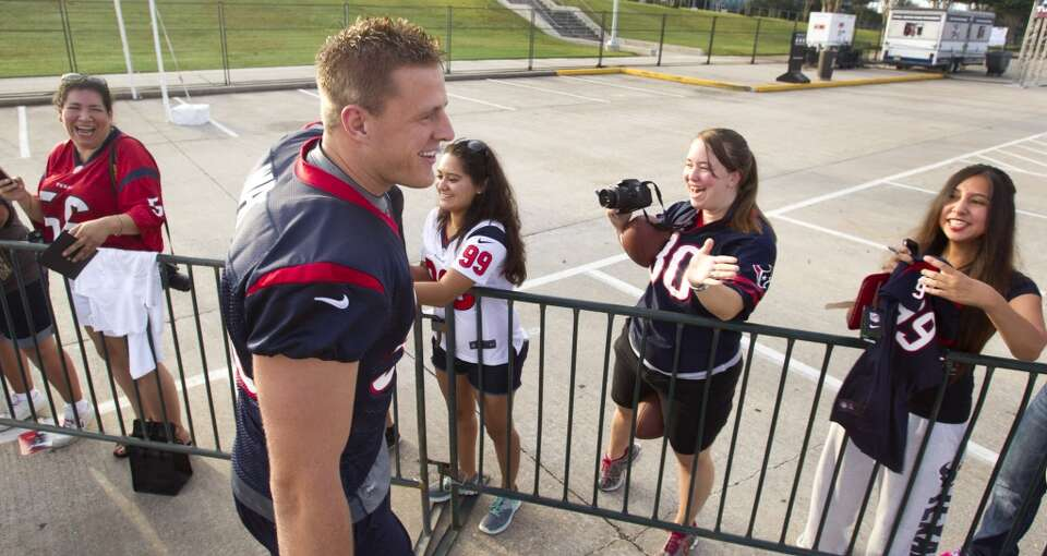 Texans defensive end J.J. Watt greets fans on his way to practice.