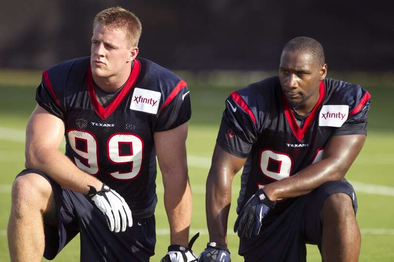 Defensive ends J.J. Watt (99) and Antonio Smith (94) take a break between drills.