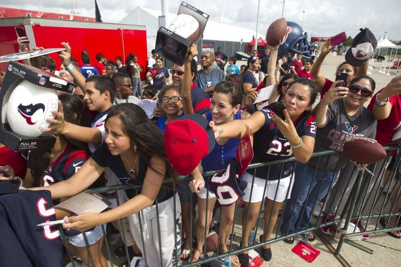 Texans fans reach out asking for autographs at the end of the first practice.